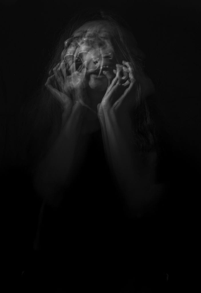 Photo by Camila Quintero Franco on Unsplash. A multilayered, black and white image of a frenzy woman scratching her face and screaming.