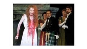 Lucia wearing a bloodstained white dress while others look on, shocked